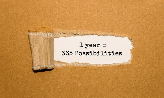 De tekst 1 jaar is 365 mogelijkheden verschijnt achter gescheurd bruin papier