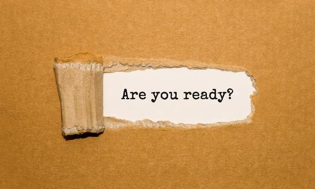 De tekst are you ready verschijnt achter gescheurd bruin papier