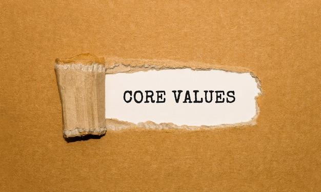 De tekst core values verschijnt achter gescheurd bruin papier