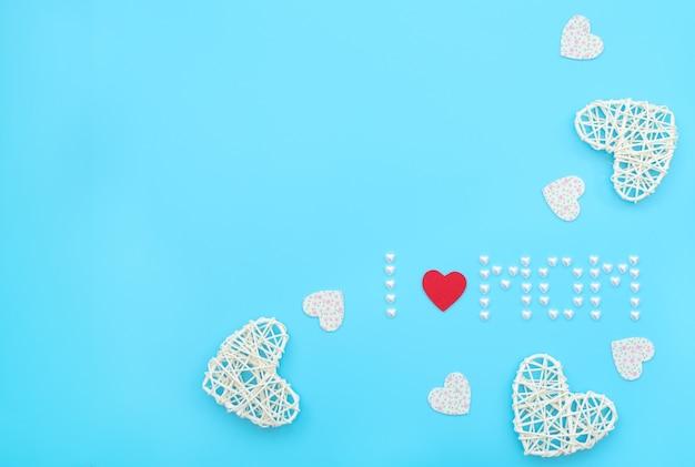 De tekst i love mom gemaakt van kleine parelhartjes met rode vilten hartjes