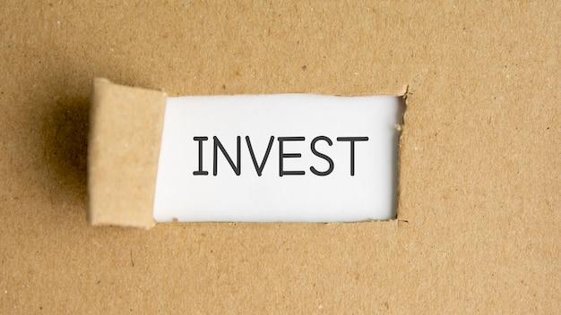 De tekst investeer achter gescheurd bruin papier