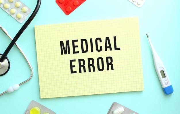 De tekst medical error is geschreven in een geel notitieboekje dat naast de stethoscoop ligt, medicijn op een blauwe achtergrond.