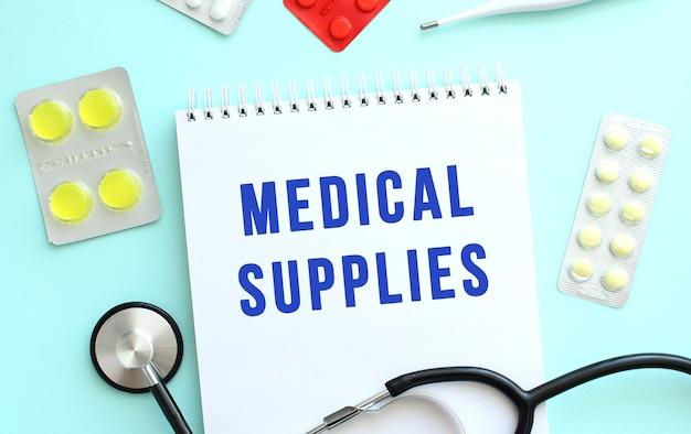 De tekst medical supplies is geschreven in een notitieboekje dat naast de stethoscoop ligt, medicijn op een blauwe achtergrond.