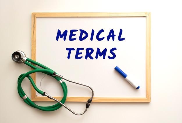 De tekst medische voorwaarden is geschreven op een wit kantoorbord met een stift. vlakbij is een stethoscoop. medisch concept.