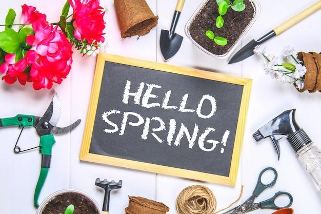 De tekst op het bord: hallo lente. hulpmiddelen om in de tuin te werken.