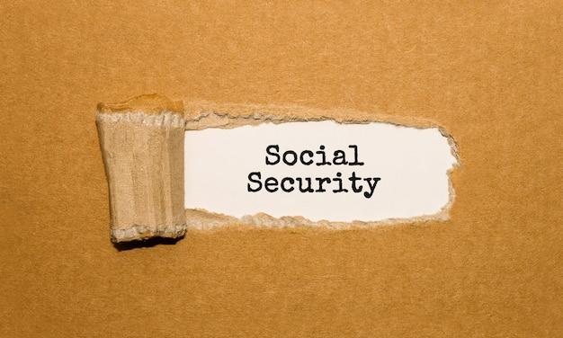 De tekst sociale zekerheid verschijnt achter gescheurd bruin papier