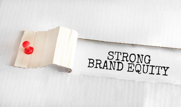 De tekst strong brand equity verschijnt achter gescheurd geel papier