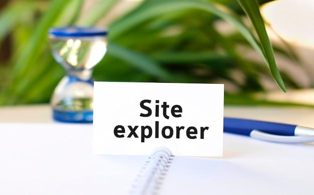 De tekst van de websiteverkenner op een wit notitieboekje en een zandloper en een blauwe pen