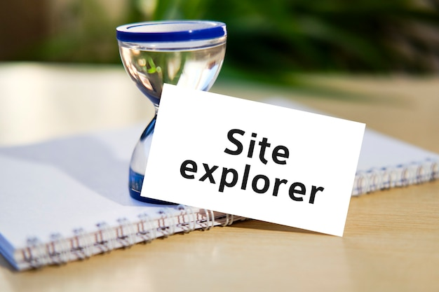 De tekst van de websiteverkenner op een wit notitieboekje en een zandloper