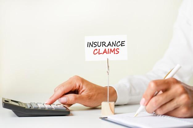 De tekst verzekeringsclaims geschreven op een witte papieren kaart geklemd in een papierhouder. op de achtergrond vrouwenhanden die met pen op papier schrijven en rekenmachine aanraken