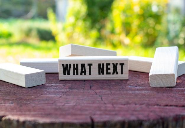 De tekst what next is geschreven op een houten kubus die op een oude boomstronk ligt tegen een wazige tuinachtergrond.