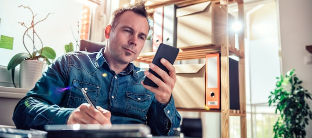 De tekstbericht van de zakenmanlezing op smartphone op het kantoor