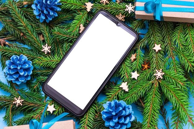 De telefoon ligt met kerstmis op de takken van een boom.