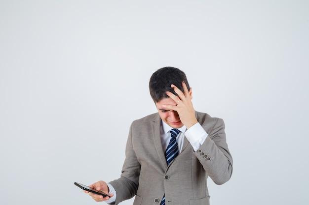 De telefoon van de jonge jongensholding, hand op hoofd zetten in formeel kostuum en gekweld op zoek. vooraanzicht.