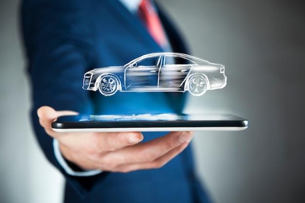 De telefoon van de zakenmanhand met auto in het scherm