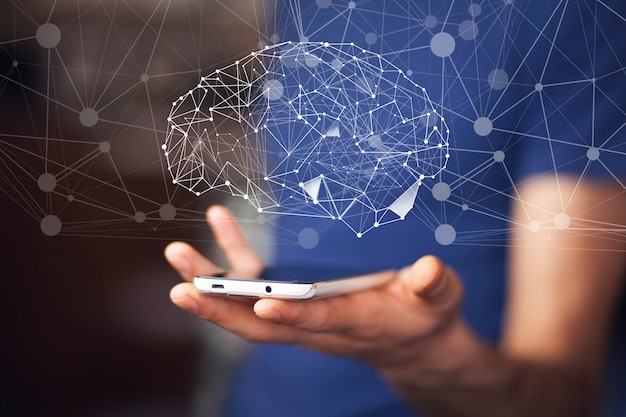 De telefoon van de zakenmanhand met digitale hersenen in het scherm