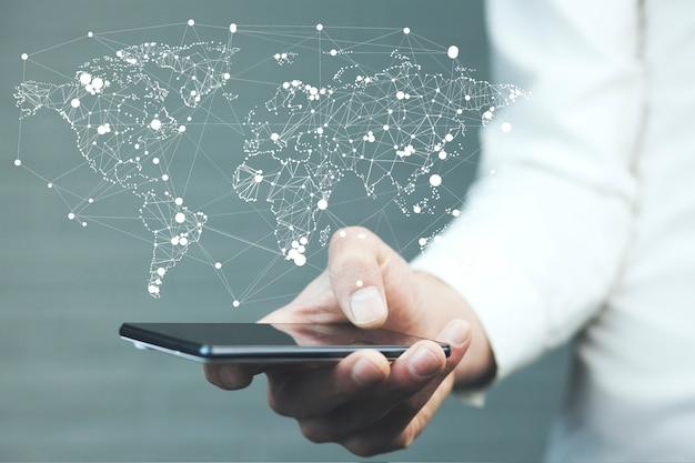 De telefoon van de zakenmanhand met wereldkaart