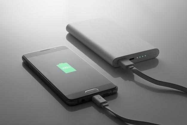De telefoon wordt opgeladen via de powerbank, in donkere tinten, 100% opgeladen