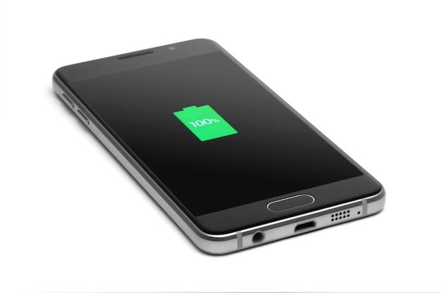 De telefoon wordt opgeladen. volledig opladen. smartphone. geïsoleerd op witte achtergrond.