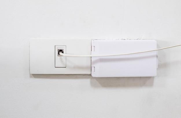 De telefoonkabel wordt aangesloten op het stopcontact op de huismuur voor de internetverbinding, adsl-internet voor gebruik in het kleine kantoor, vooraanzicht met de kopieerruimte.