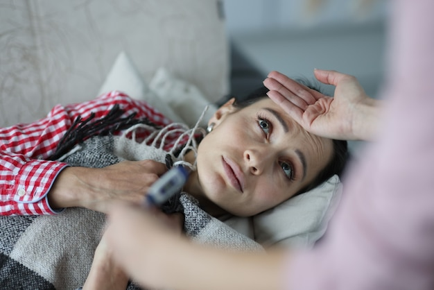 De temperatuur van een zieke vrouw wordt op bed gemeten. verkoudheid concept
