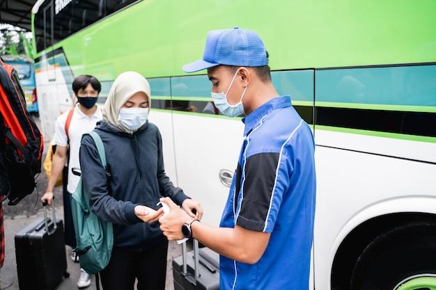 De tempratuur van aziatische passagiers controleren en met de hand ontsmetten voordat ze in een bus gaan rijden