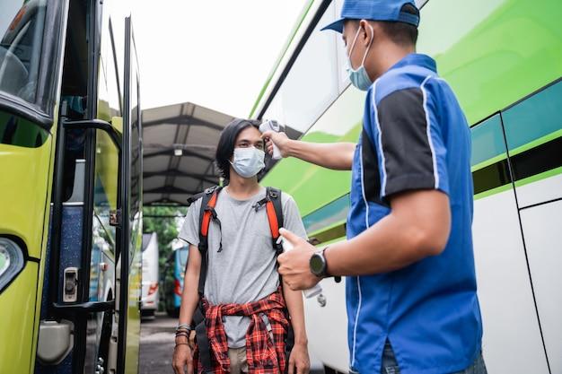 De tempratuurcontrole van de aziatische passagier met behulp van thermogun voordat de bus wordt gereden