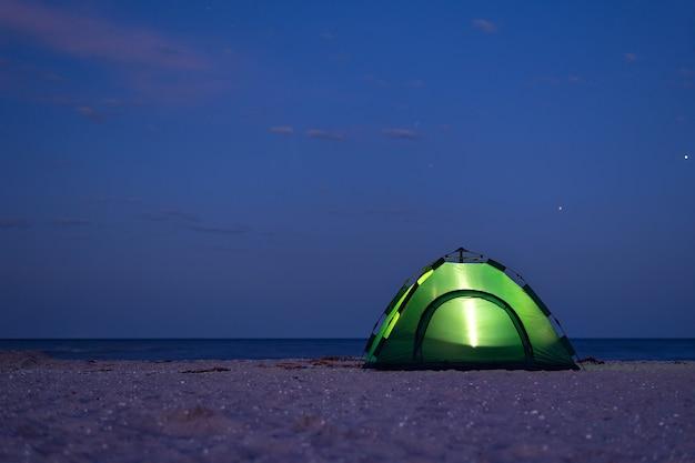 De tent is 's nachts verlicht. tent onder de sterrenhemel aan de kust