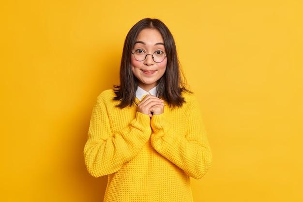 De tevreden aziatische vrouw houdt de handen bij elkaar en verwacht iets goeds glimlacht zachtjes heeft kuiltjes op de wangen gekleed in vrijetijdskleding.
