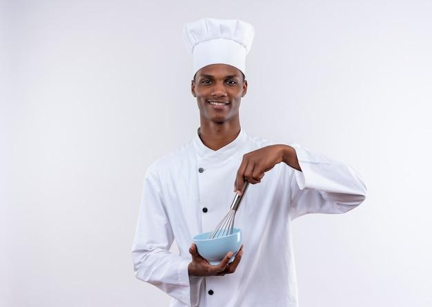 De tevreden jonge afro-amerikaanse kok in eenvormige chef-kok houdt kom en zwaait op geïsoleerde witte achtergrond met exemplaarruimte