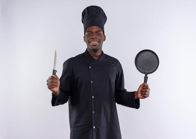 De tevreden jonge afro-amerikaanse kok in eenvormige chef-kok houdt mes en koekenpan op wit met exemplaarruimte