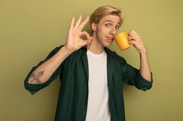 De tevreden jonge blonde kerel die groen t-shirt draagt, drinkt thee en toont oke gebaar