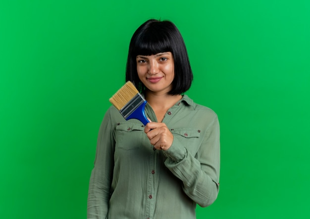 De tevreden jonge donkerbruine kaukasische vrouw houdt verfborstel op groene achtergrond met exemplaarruimte wordt geïsoleerd die