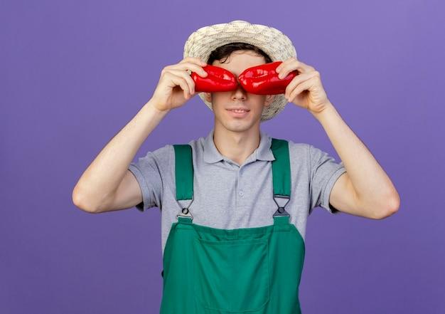 De tevreden jonge mannelijke tuinman die tuinierende hoed draagt, behandelt ogen met peper