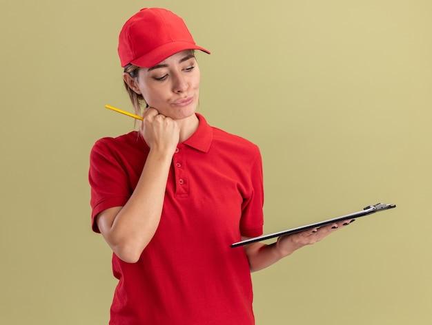 De tevreden jonge mooie leveringsvrouw in uniform legt de hand op het potlood van de kinholding en kijkt naar het klembord dat op de olijfgroene muur wordt geïsoleerd