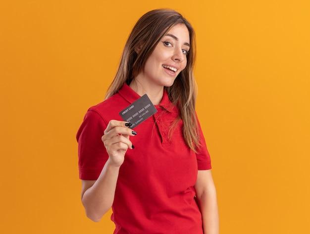 De tevreden jonge mooie vrouw houdt creditcard die op oranje muur wordt geïsoleerd