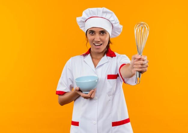 De tevreden jonge vrouwelijke kok die kom van de chef-kok het eenvormige holdings stand houden zwaait op geïsoleerde gele muur met exemplaarruimte