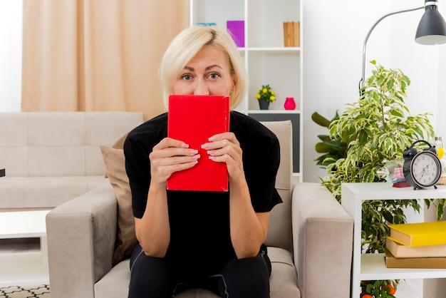 De tevreden mooie blonde russische vrouw zit op leunstoelholding en kijkt uit over boek