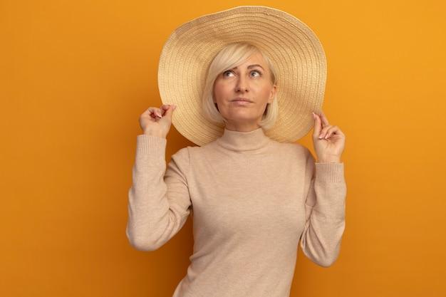 De tevreden mooie blonde slavische vrouw met strandhoed kijkt omhoog op sinaasappel