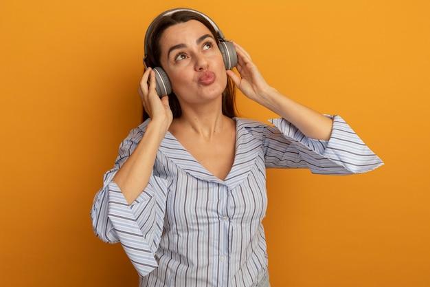 De tevreden mooie vrouw op hoofdtelefoons wordt geïsoleerd op oranje muur opgezocht