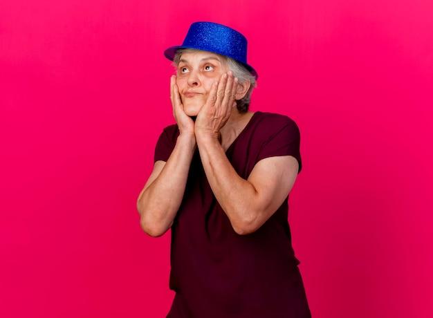 De tevreden oudere vrouw die een feestmuts draagt, legt de handen op het gezicht en kijkt omhoog op roze