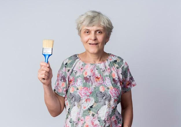 De tevreden oudere vrouw houdt verfborstel op witte muur wordt geïsoleerd die