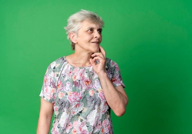 De tevreden oudere vrouw legt hand op kin die kant bekijkt die op groene muur wordt geïsoleerd