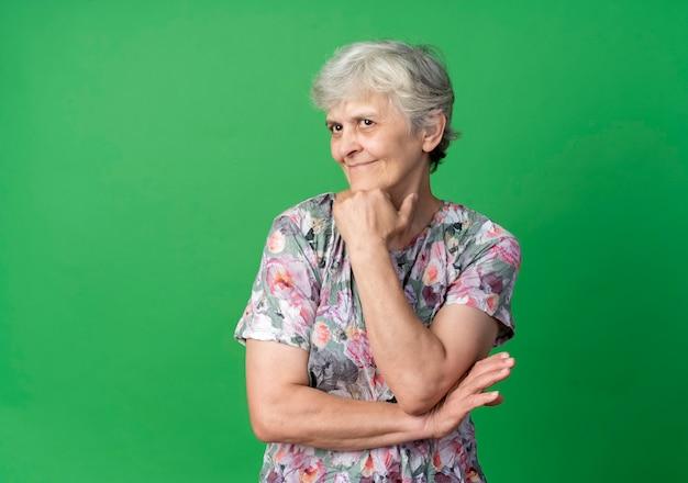 De tevreden oudere vrouw legt hand op kin die op groene muur wordt geïsoleerd
