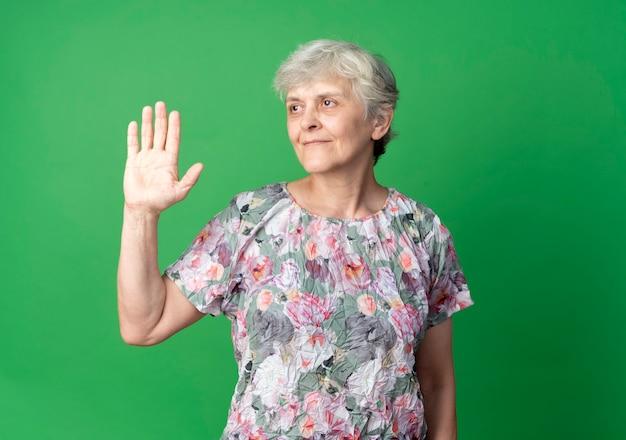 De tevreden oudere vrouw steekt hand op die kant bekijkt die op groene muur wordt geïsoleerd