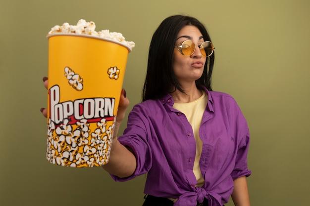 De tevreden vrij donkerbruine kaukasische vrouw in zonnebril houdt geïsoleerde emmer popcorn