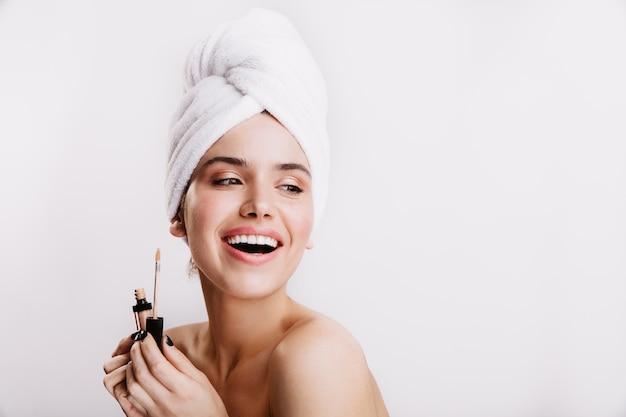 De tevreden vrouw in handdoek op haar hoofd glimlacht op witte muur. dame met blote schouders houdt concealer vast.