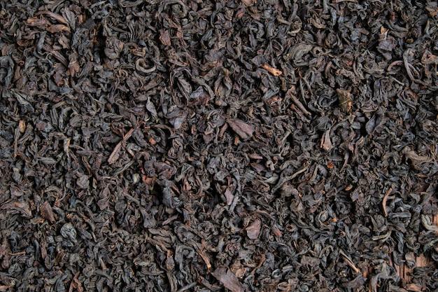 De textuur en achtergrond van zwarte thee. bovenaanzicht