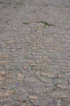 De textuur is zeer oud en onnauwkeurig aangelegde straatstenen gemaakt van reliëfstenen van verschillende vormen