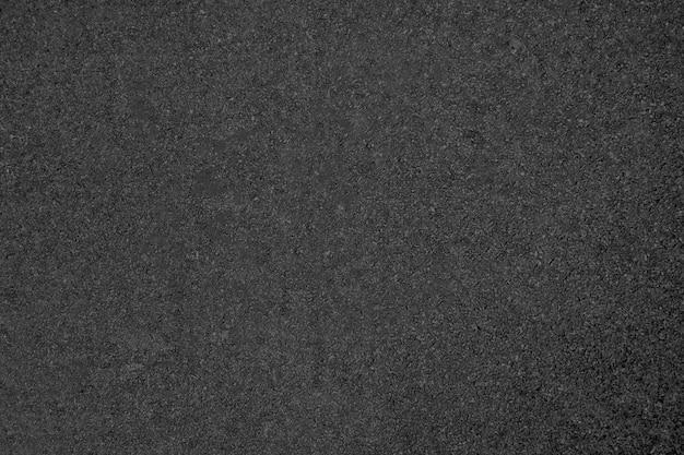 De textuur van de asfaltweg in donkergrijze kleur